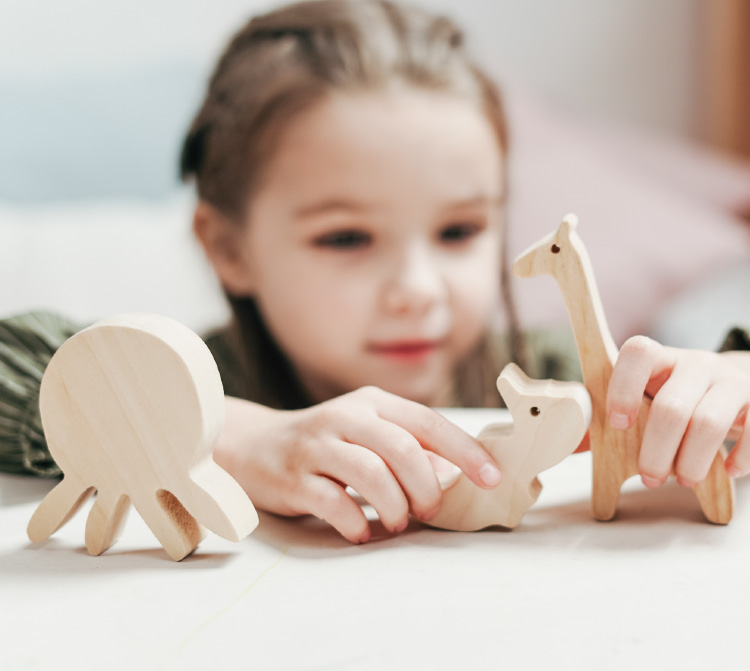 child playing with wooden animals
