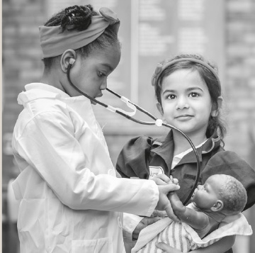 child playing doctor with a stethoscope and dolly