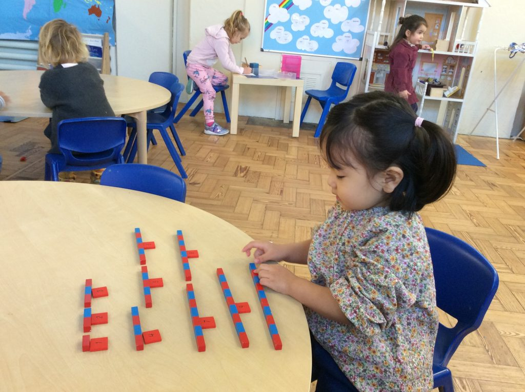 nursery child learning maths with red and blue blocks