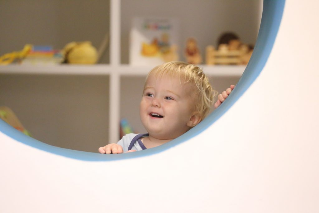 toddler boy looking through large hole in wall
