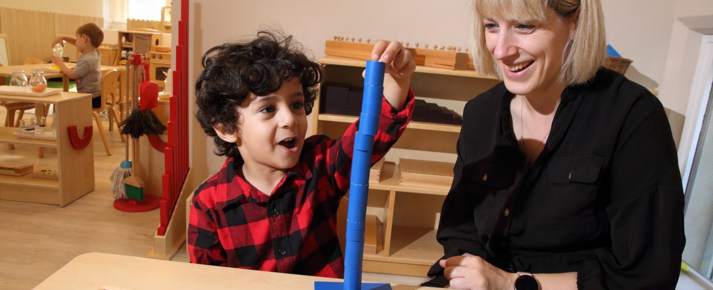 little boy making a blue tower with building blocks