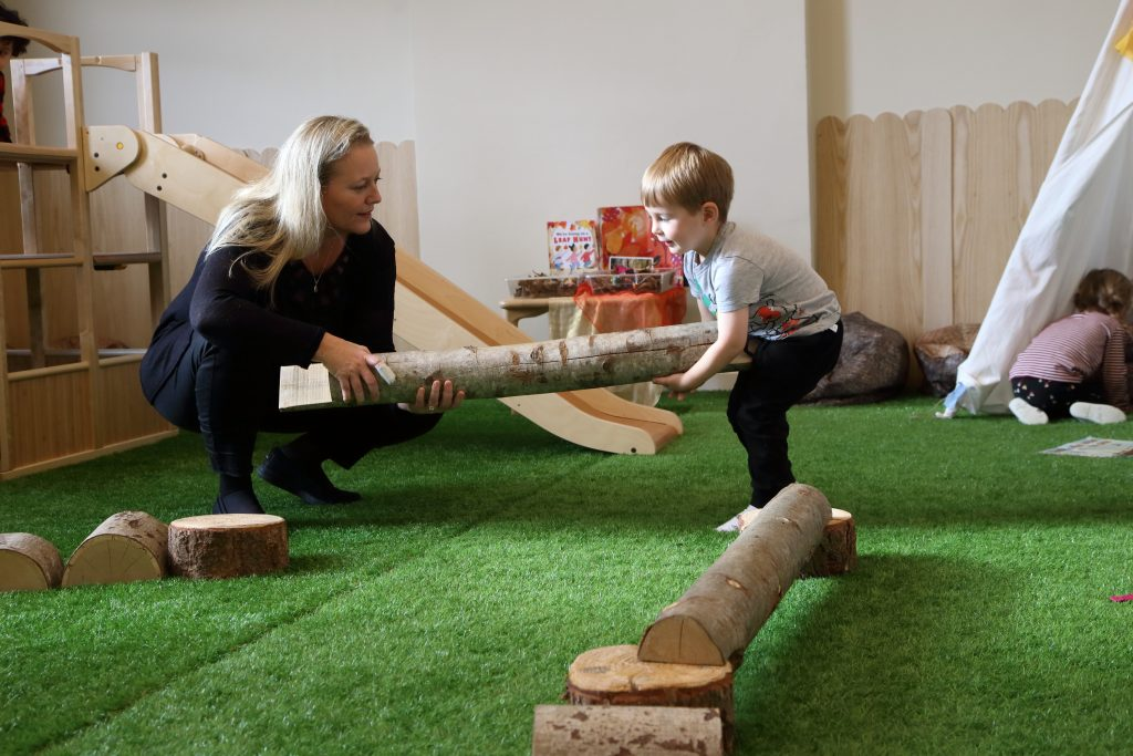 child and teacher carrying a log