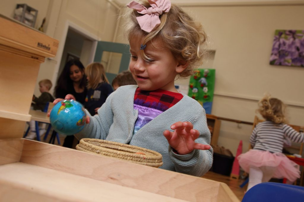little girl in classroom holding a small globe