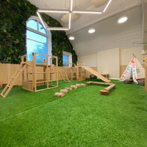 An inside play area for children in the nursery, with wooden climbing frames, a tipi and astro turf