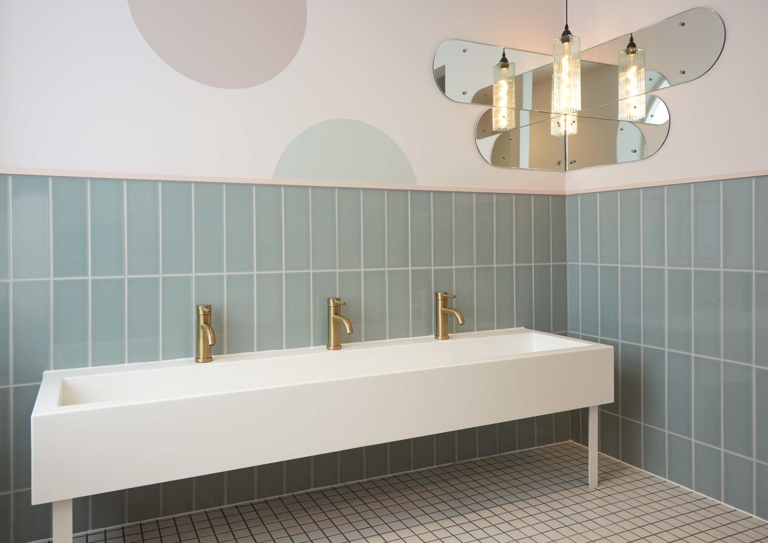 A bathroom with light blue tiles on the walls, white tiles on the floor and a long horizontal sink with 3 gold taps