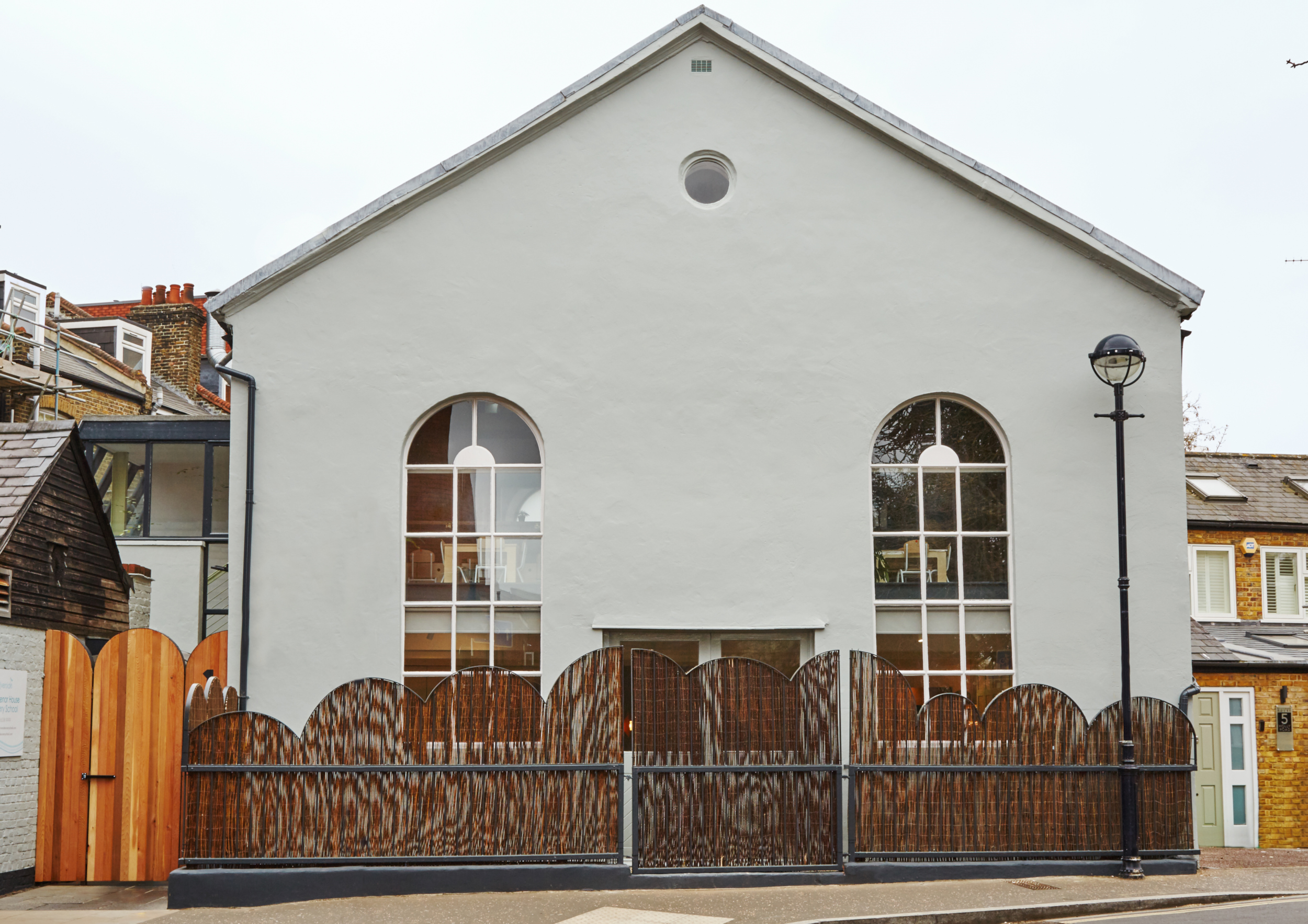 The exterior of the nursery. It's a tall off-white building with a large pointed roof and two arched windows and arched fencing to reflect the window shape