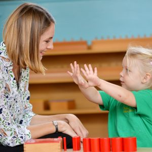 A teacher looking at a child who is putting their hands out towards them