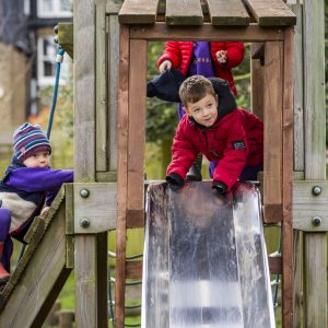 A young boy wearing a dark red coat about to go down the slide headfirst