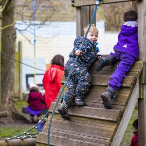 Young children going up a climbing frame wrapped up in warm suits during the cold weather